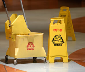 mop bucket and caution sign preventing slip and fall injury