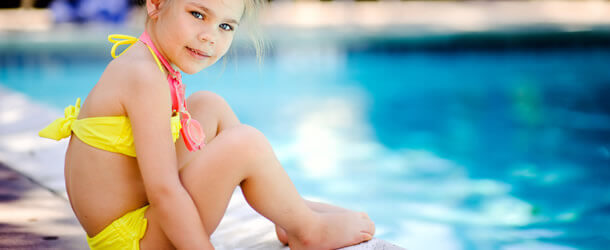 young girl sitting next to pool