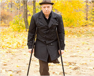 elderly man on crutches with amputated leg